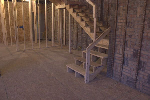 The staircase in the south condo. The stairs will feature a glass railing. Kitchen cupboards will be built beneath the stairs, and the refrigerator will be underneath the landing. (photo by Dawn Olsen)