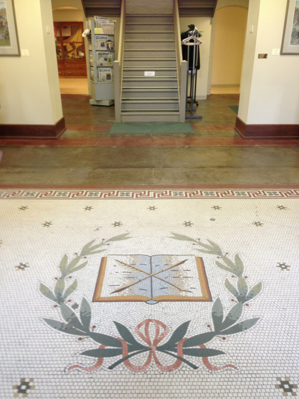 Restored original floor mosaic in front of a non-origianal staircase, situated where the librarian's desk would have been located. - Photo by Ryan Hamlett