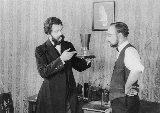 Inventor Alexander Graham Bell (1847-1922) shows his first telephone to assistant Thomas Augustus Watson (1854-1934) (photo courtesy of wired.com)