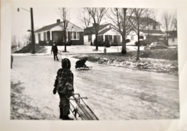 Alice sledding with her friends, looking out from 6045 Primrose Ave.