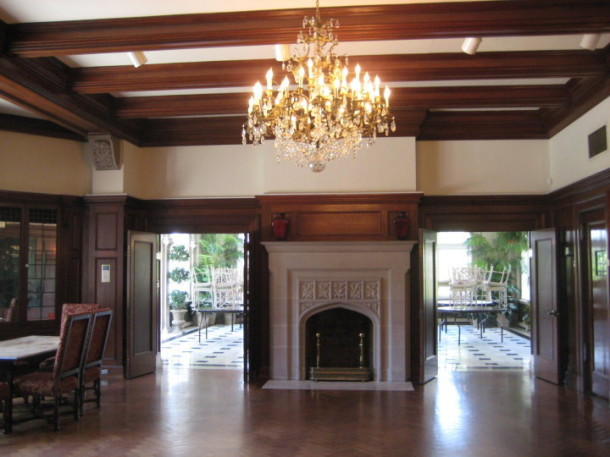 Laurel Hall: a lower dining room that opens into a palm tree-lined solarium with marble floors.