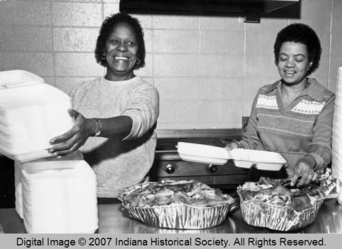 Volunteers prepare plates for guests of the Mozel Sanders Thanksgiving Day Dinner in 1983.