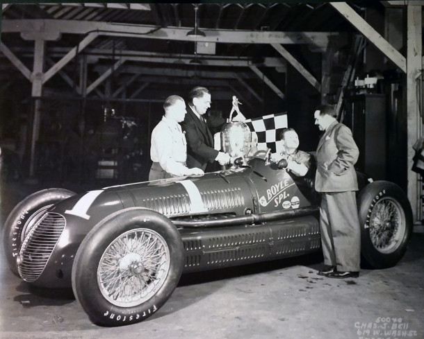 Indianapolis 500 race winner Wilbur Shaw in his Boyle special and with his trophy inside the building at 1701 Gent Avenue   (1940 photo courtesy of Indiana Motor Speedway)