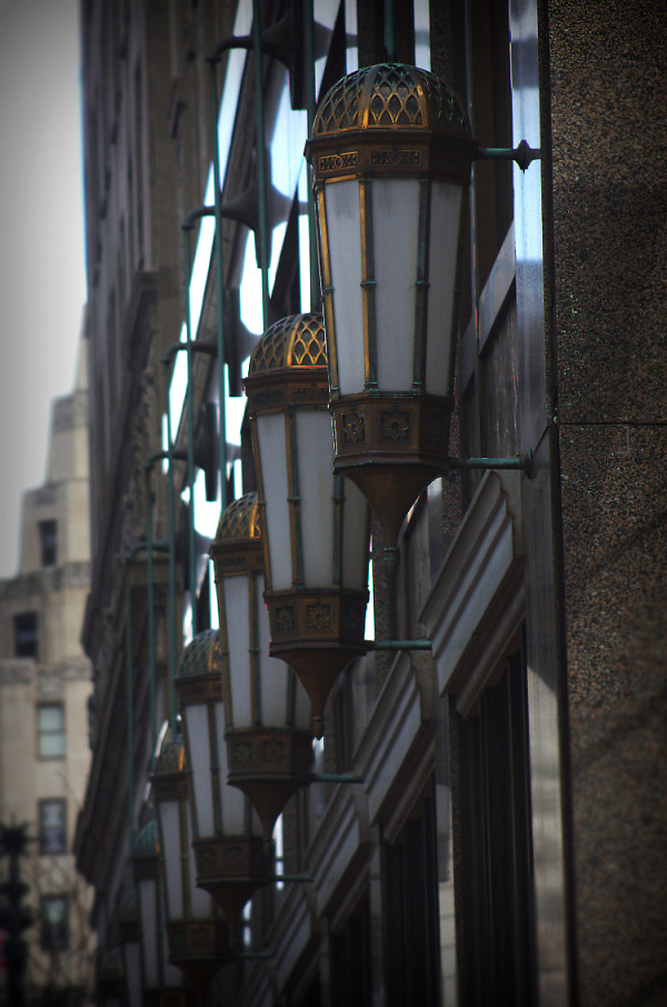 Bronze light fixtures line the exterior of the Illinois Building. The City Tower building lurks in the background, across Monument Circle. (Photo by Dawn Olsen)