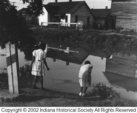 Two girls fishing for crayfish on the Indiana Central Canal in Indianapolis in 1946.