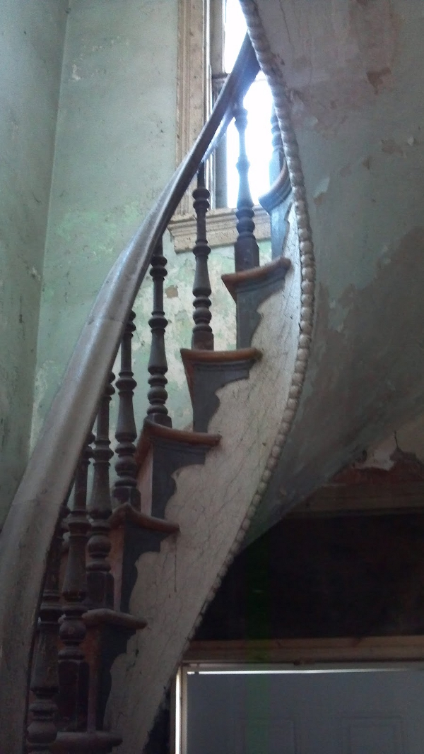 The spiral staircase, located in the front entryway, is open string, and relies on the exterior walls of the home for support.
