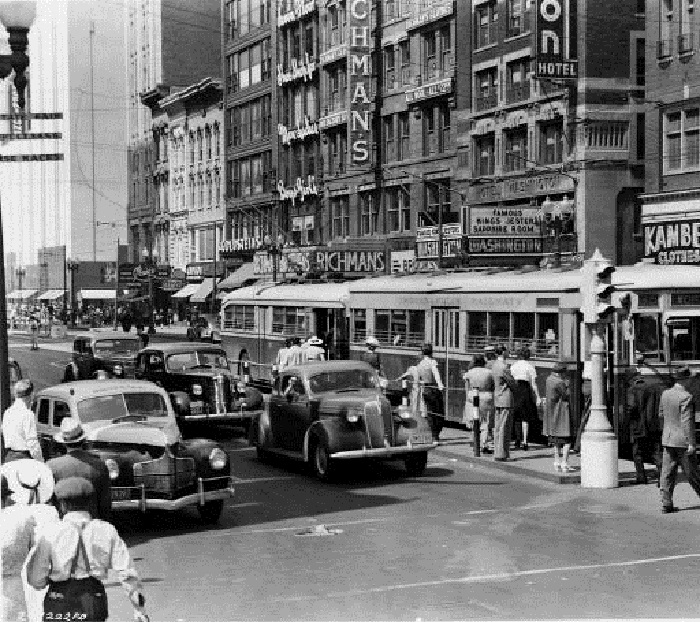 "A street scene in front of the Hotel Washington in 1940. It contains many things city residents long for today: bustling streets, active retail, and mass transit. The marquee of the hotel is advertising ""Famous King's Jester"" in the Sapphire Lounge(courtesy Indiana Historical Society)"