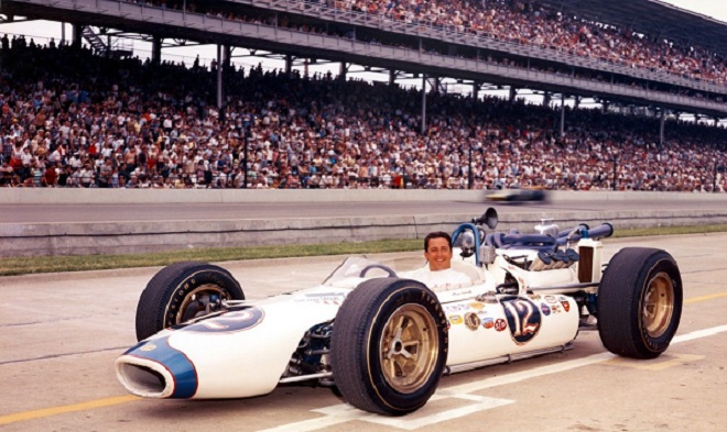 A young Mario Andretti poses in his number 12 Ford after qualifying for the 1965 Indianapolis 500. This would be the car that would win the Hoosier Grand Prix two months later. The following year Andretti would sport the number 1 in honor of his series championship in '65 (Courtesy eBay)